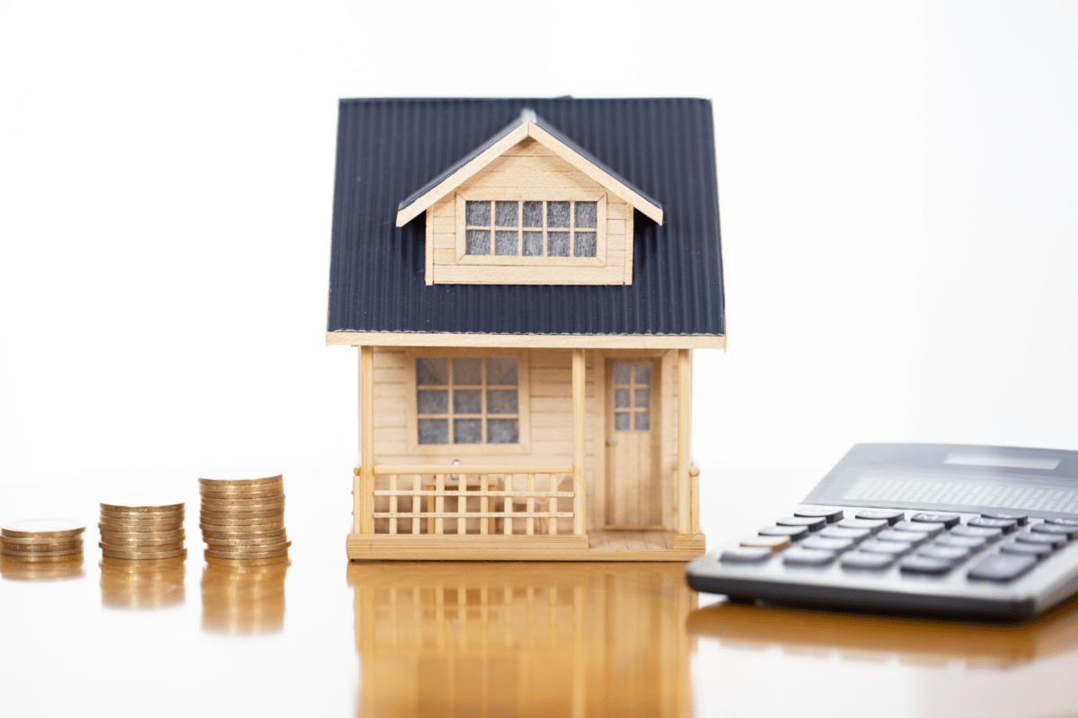 settlement costs: miniature house with calculator and coins